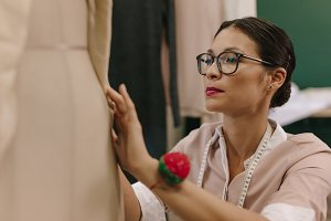 Fashion designer fixing dress