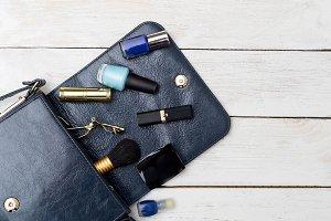 Handbag of blue color and cosmetics