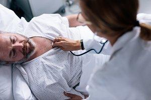 Doctor taking heartbeats of sick