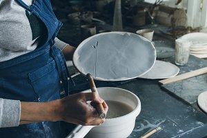 Woman painting a clay dish