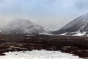 Large mountains covered with snow and fog