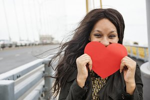 Woman holding heart shaped paper