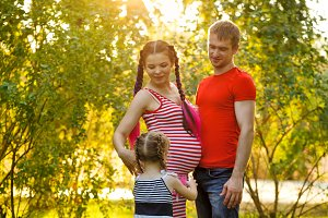 Husband, pregnant wife and daughter