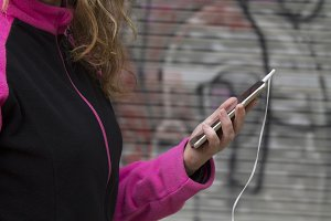Woman athlete listening music with mobile phone