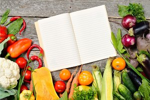 Open recipe book with set of raw organic vegetables on vintage wooden table