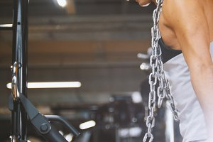 Muscular man in the gym performs exercises pull up with metal chain