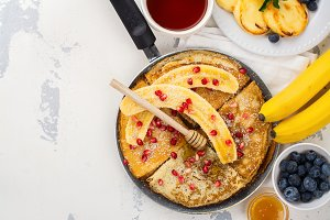 Sweet crepes with banana, honey and pomegranate seeds