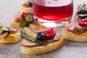 Bruschetta sandwiches with duck meat and berries
