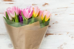 Tulips wrapped on brown paper on light background