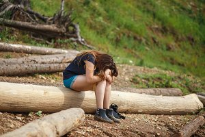 A young woman is sitting on a fallen tree. She has hung the head. Concept of fatigue