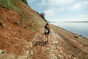 Girl Explores Steep Rocky Banks of the River Situated in Taiga Forest