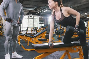 Woman athlete lifting dumbbells in the gym - coach observing training