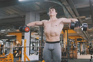 Athlete man lifting dumbbells without shirt in the gym