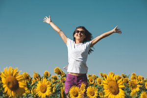 Beautiful young girl with blue hair standing in a field with sunflowers with full hands and smiling