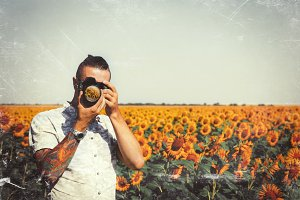 Man Photographer In Sunflower Meadowflower garden With DSLR Camera