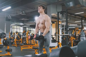 Muscular sportsman in the gym lifting dumbbells without shirt