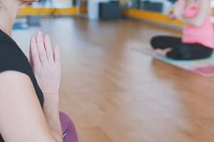 Coach shows lotus pose for group of women - yoga in the gym