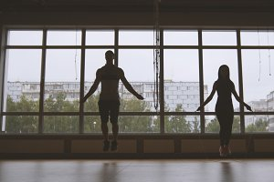 Fitness in the gym - sporty woman and muscular man jumps on rope near window, silhouette