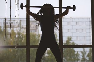 Girl in the gym lifting up the barbell - silhouette