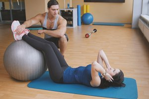 Sportive young woman with fitness instructor doing abdominal crunches on fitballs