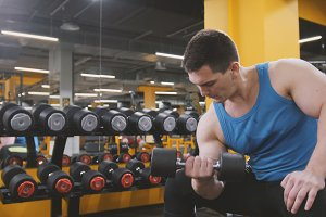 Weight-lifting in the gym - muscular athlete performs training for biceps with dumbbells