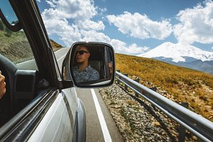 Driver enjoy view on mountain road. Man face is reflected in side view mirror