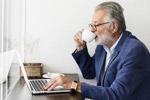 Elderly man is using laptop