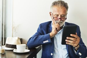 Elderly man is using tablet