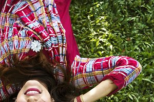 Indian woman is lying on grass