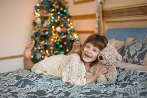 Girl with bear on bed near christmas