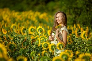 Woman among yellow sunflowers.