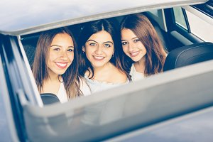 Smiling girls friends in a car
