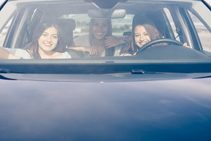 Girl drives a car with girls friends