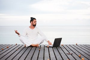 Man in white clothes meditating yoga with laptop on wooden pier