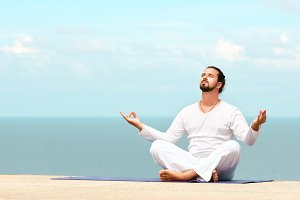 Man in white clothes meditating yoga on the sea shore