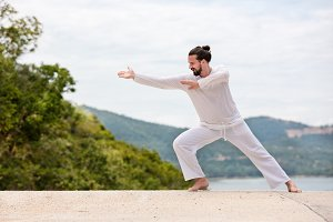 Kickboxer or muay thai fighter Man in white training karate  Wushu on mountain