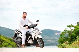 Brutal biker with beard wearing white sitting on motorbike in mountains.