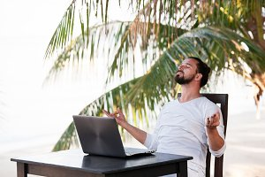 Man relaxing on the beach and doing yoga with laptop, freelancer workplace, dream job