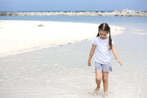 Happy child on the beach. Paradise holiday concept, girl seating on sandy beach with blue shallow water and clean sky