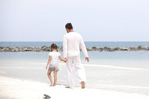 Adorable little girl holding her father hand. Father and daughter playing together at the beach.