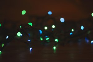 Christmas lights on wooden table.