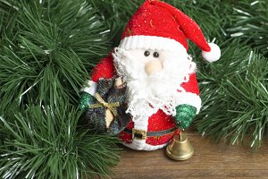 Christmas decoration of Santa Claus next to Christmas tree on wooden table.