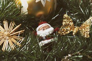 Christmas decoration with ball and golden butterfly next to santa claus on Christmas tree.
