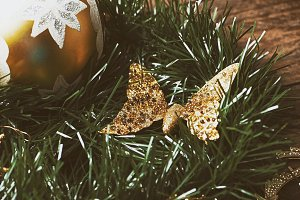 Christmas decoration with ball and golden butterfly on christmas tree.