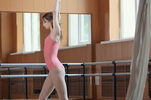 A young girl gracefully performs acrobatics tricks in studio