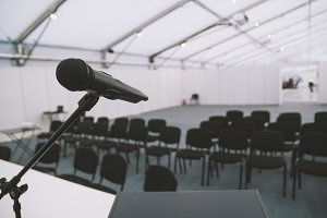 Black microphone in conference room - empty chairs on background