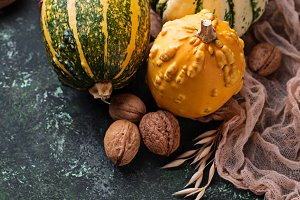 Autumn background with pumpkins and nuts.