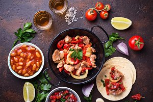 Concept of Mexican food.  Salsa, tortilla, beans, fajitas and te