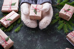 Hands in mittens holding a Christmas gift box