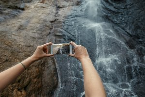 Unrecognizable Tourist Taking Photos Of Waterfall With Mobile Phone. Travel Adventure Destination Outdoor Concept